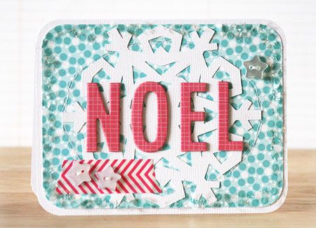 aqua coloured patterned card with star shaped buttons and noel lettering